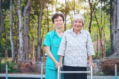 Smiling caregiver Senior nurse take care a Senior patient in walker for relaxing and looking around park royalty free stock photography