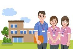 Smiling caregivers with nursing facility Stock Image