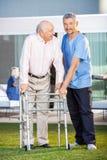 Smiling Caretaker Assisting Senior Man To Use stock photo