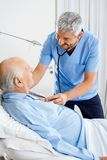 Smiling Caretaker Checking Senior Man's Chest. Smiling male caretaker checking senior man's chest with stethoscope in bedroom at nursing home royalty free stock photos