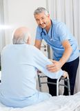 Smiling Caretaker Helping Senior Man With Walking Royalty Free Stock Photos