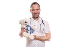 Smiling caring paediatricain holding a teddy bear Stock Photos