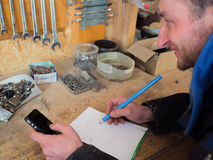 Smiling carpenter calculating with smart-phone Royalty Free Stock Photos
