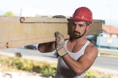 Smiling Carpenter Carrying A Large Wood Plank On His Shoulder Stock Photo