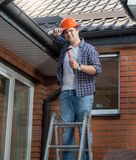 Portrait of smiling carpenter in hardhat standing on top of stepladder. Smiling carpenter in hardhat standing on top of stepladder Royalty Free Stock Image