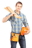 Smiling carpenter holding a helmet and sills. Isolated on white background Royalty Free Stock Photography
