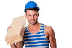 Smiling carpenter holding planks Stock Photo