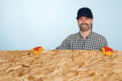 Smiling carpenter holds plywood Royalty Free Stock Photos