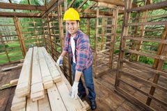 Smiling Carpenter Measuring Wooden Plank At Royalty Free Stock Photos
