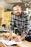Smiling carpenter planning work in the workshop Stock Photography