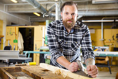 Smiling carpenter work with plane on wood plank in workshop Stock Photography
