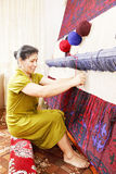 Smiling carpet weaver sideview Royalty Free Stock Photography