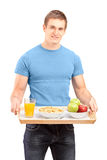 A smiling carrying a wooden tray with drinks and food Royalty Free Stock Photos