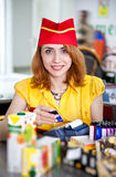 Smiling cashier girl in red and yellow uniform Stock Photo