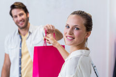 Smiling cashier giving shopping bag to woman Stock Image