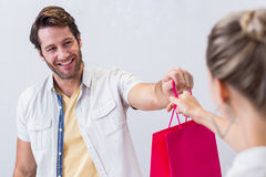 Smiling cashier giving shopping bag to woman Royalty Free Stock Photos
