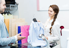 Smiling cashier and satisfied customer. At checkout desk royalty free stock photos
