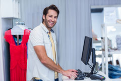 Smiling cashier typing Stock Photography