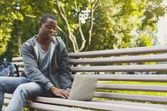 Happy young african-american student with laptop outdoors. Smiling casual african-american student working with laptop in the park in pleasant atmosphere Royalty Free Stock Image