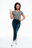 Smiling casual african woman standing and showing ok gesture. Full length portrait of a smiling casual african woman standing and showing ok gesture isolated Stock Images