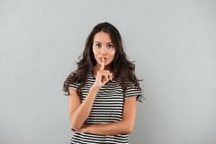 Smiling casual asian woman showing silence gesture. With finger over her lips isolated over gray background Stock Photography
