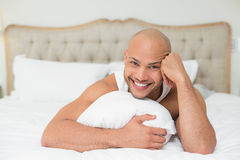 Smiling casual bald young man lying in bed Royalty Free Stock Photography