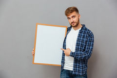 Smiling casual bearded man pointing finger at blank board Royalty Free Stock Photos