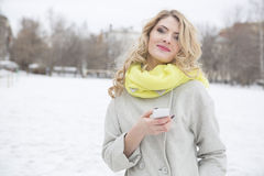 Smiling casual blonde text messaging outdoors Royalty Free Stock Photos