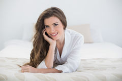 Smiling casual brown haired woman in white pajamas lying on her bed Royalty Free Stock Images