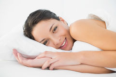 Smiling casual brunette lying in her bed Royalty Free Stock Photography