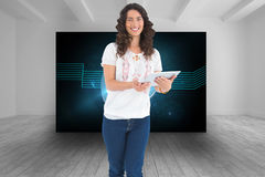 Smiling casual brunette using her tablet pc. Composite image of smiling casual brunette using her tablet pc Royalty Free Stock Photos