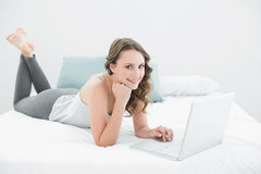 Smiling casual brunette using laptop in bed Royalty Free Stock Photos
