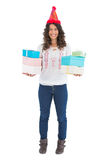 Smiling casual brunette wearing party hat holding presents Stock Photo