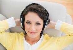 Smiling casual brunette in yellow cardigan enjoying music Royalty Free Stock Photos
