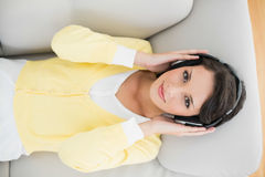 Smiling casual brunette in yellow cardigan listening to music with headphones Royalty Free Stock Image