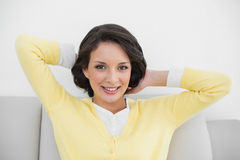 Smiling casual brunette in yellow cardigan posing looking at camera Royalty Free Stock Images