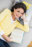Smiling casual brunette in yellow cardigan reading a book Royalty Free Stock Photography