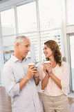 Smiling casual business colleagues having coffee together Stock Photos