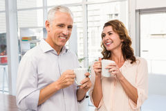 Smiling casual business colleagues having coffee together Stock Photography