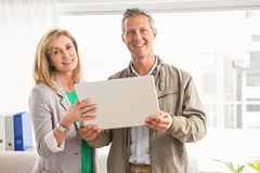 Smiling casual business colleagues with laptop Stock Images