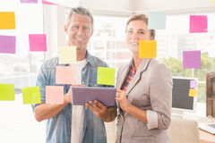 Smiling casual business colleagues with tablet Royalty Free Stock Photography