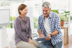 Smiling casual business colleagues using tablet Royalty Free Stock Photography