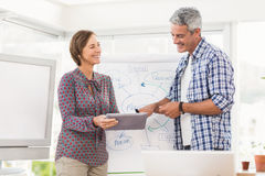 Smiling casual business colleagues using tablet Stock Images