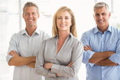 Smiling casual business people with arms crossed. Portrait of smiling casual business people with arms crossed in the office Stock Photo