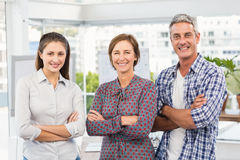 Smiling casual business people with arms crossed. Portrait of smiling casual business people with arms crossed in the office Royalty Free Stock Photos
