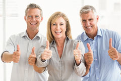 Smiling casual business people doing thumbs up Royalty Free Stock Photo