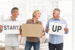 Smiling casual business people holding start up sign Royalty Free Stock Photography