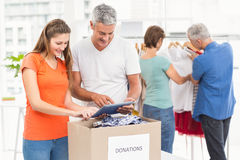 Smiling casual business people sorting donations. In the office royalty free stock photography