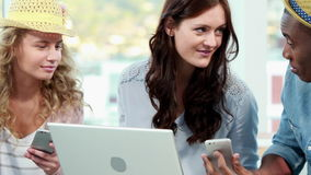 Smiling casual business team using electronic devices. In the office stock footage
