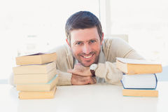 Smiling casual businessman with books at his desk Stock Photography